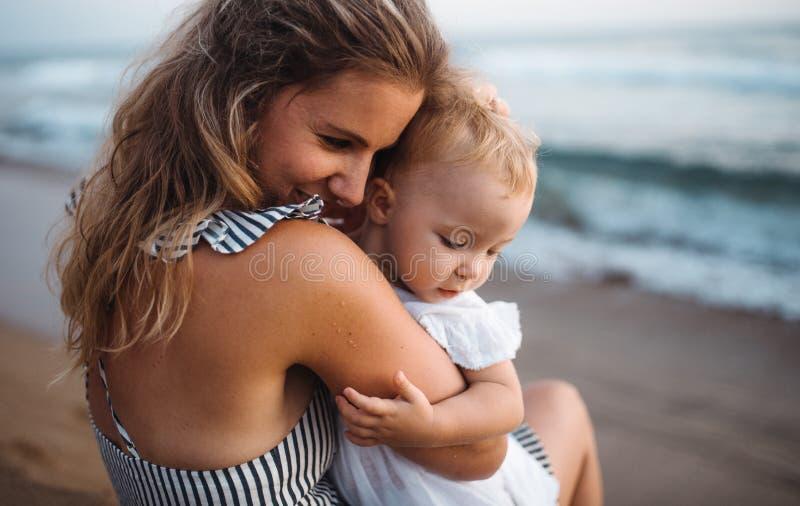 Κινηματογράφηση σε πρώτο πλάνο της νέας μητέρας με ένα κορίτσι μικρών παιδιών στην παραλία στις καλοκαιρινές διακοπές στοκ φωτογραφία με δικαίωμα ελεύθερης χρήσης