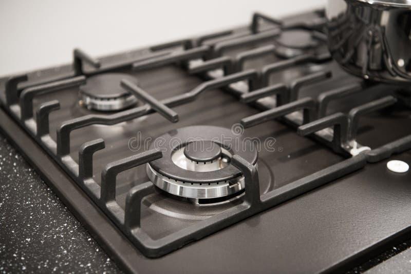 Κινηματογράφηση σε πρώτο πλάνο της ολοκαίνουργιας, σύγχρονης σόμπας αερίου countertop στη σύγχρονη σύγχρονη εγχώρια κουζίνα στοκ εικόνα