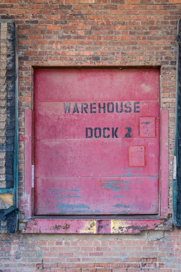 Κινηματογράφηση σε πρώτο πλάνο της παλαιάς κόκκινης πόρτας αποβαθρών αποθηκών εμπορευμάτων στο τουβλότοιχο στοκ εικόνες