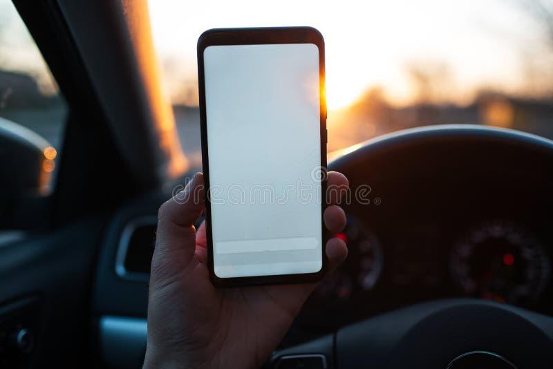 Κινηματογράφηση σε πρώτο πλάνο της παράδοσης του smartphone με το πρότυπο στο αυτοκίνητο στοκ φωτογραφία με δικαίωμα ελεύθερης χρήσης