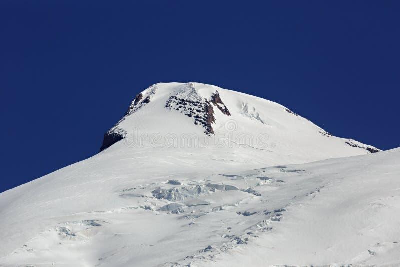 Κινηματογράφηση σε πρώτο πλάνο της χιονισμένης δυτικής αιχμής του υποστηρίγματος Elbrus στοκ φωτογραφία