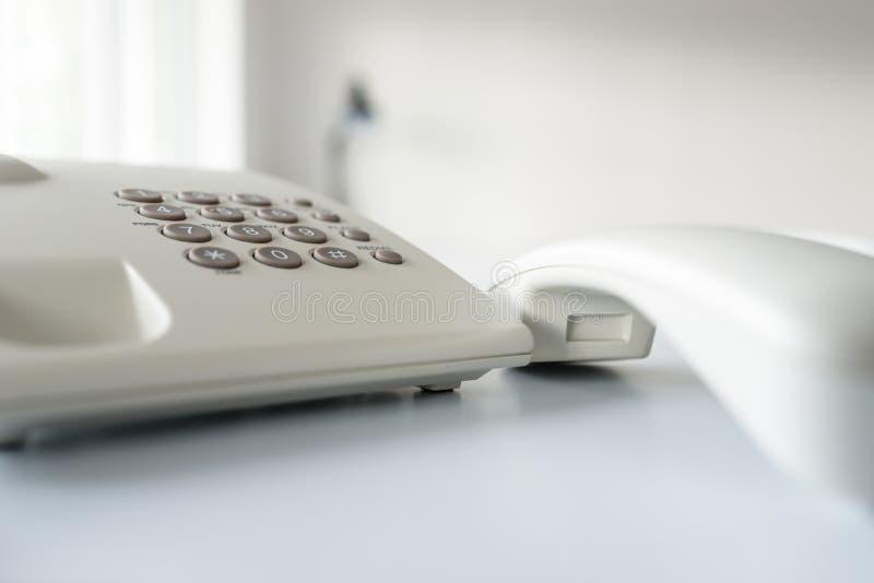 Κινηματογράφηση σε πρώτο πλάνο του άσπρου τηλεφώνου γραμμών εδάφους με το μικροτηλέφωνο από το γάντζο στοκ φωτογραφία με δικαίωμα ελεύθερης χρήσης