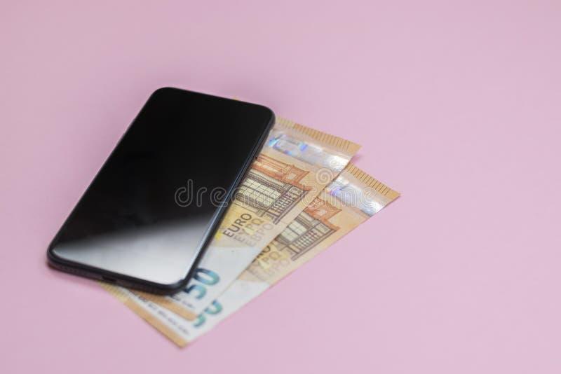 Κινηματογράφηση σε πρώτο πλάνο του έξυπνου τηλεφώνου με τα χρήματα σε ένα ρόδινο υπόβαθρο στοκ φωτογραφία