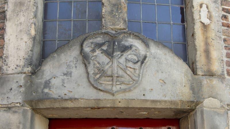 Κινηματογράφηση σε πρώτο πλάνο του αετώματος Stone για τη συντεχνία του σιδηρουργού επάνω από μια κόκκινη πόρτα, σπίτι Waag, Άμστ στοκ φωτογραφία με δικαίωμα ελεύθερης χρήσης
