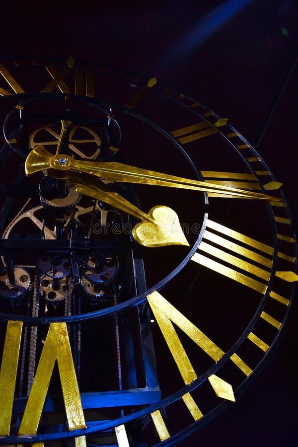 Κινηματογράφηση σε πρώτο πλάνο του αρχαίου σκοτεινού ρολογιού σκελετών με τα χρυσά χέρια και τους ρωμαϊκούς αριθμούς στοκ φωτογραφία με δικαίωμα ελεύθερης χρήσης