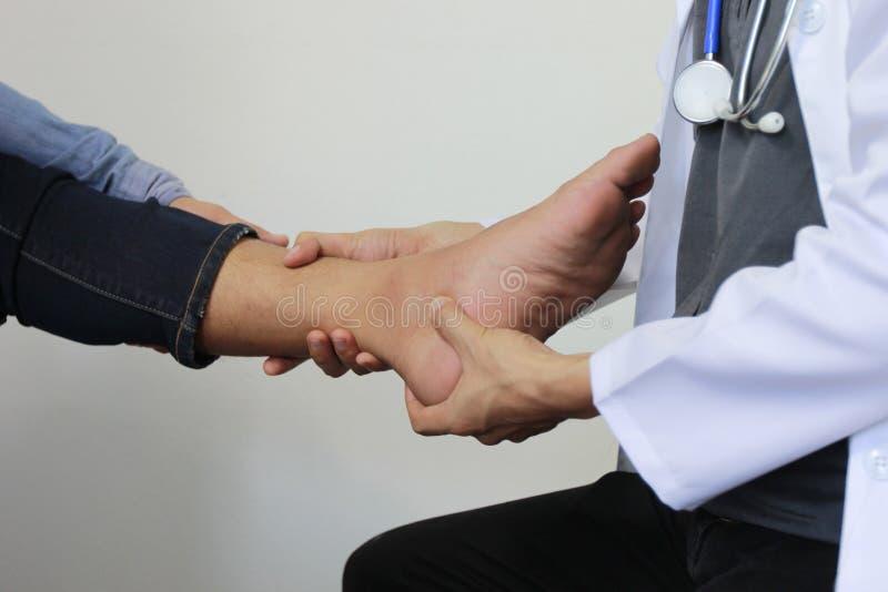Κινηματογράφηση σε πρώτο πλάνο του ατόμου που αισθάνεται τον πόνο στο πόδι και το γιατρό της το traumatol στοκ φωτογραφία
