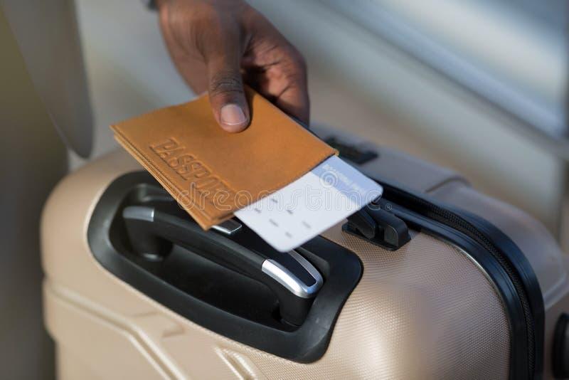Κινηματογράφηση σε πρώτο πλάνο του αφρικανικών ανθρώπινων διαβατηρίου εκμετάλλευσης χεριών, των αποσκευών και του εισιτηρίου αερο στοκ φωτογραφία