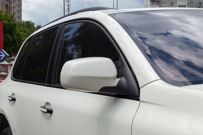 Κινηματογράφηση σε πρώτο πλάνο του δευτερεύοντος αριστερού καθρέφτη με το παράθυρο του σώματος αυτοκινήτων άσπρο SUV στο χώρο στά στοκ εικόνα