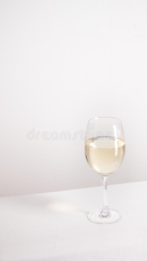 Κινηματογράφηση σε πρώτο πλάνο του διαφανούς σαφούς ποτηριού κρυστάλλου του άσπρου κρασιού στοκ φωτογραφία με δικαίωμα ελεύθερης χρήσης
