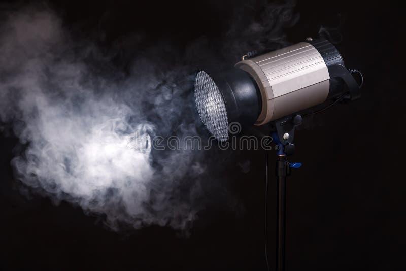 Κινηματογράφηση σε πρώτο πλάνο του επαγγελματικού φωτός στούντιο Έννοια photoshoot στην ομίχλη στοκ εικόνες