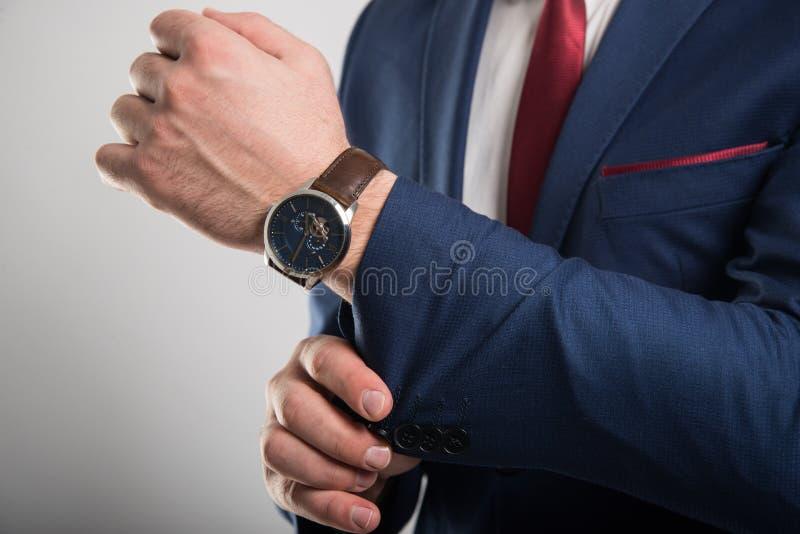 Κινηματογράφηση σε πρώτο πλάνο του επιχειρησιακού ατόμου που φορά το κοστούμι που τακτοποιεί το μανίκι σακακιών στοκ εικόνες