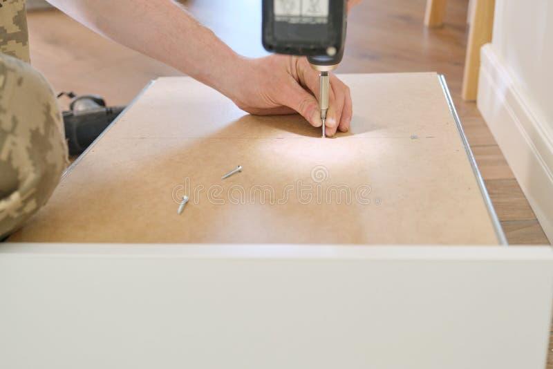 Κινηματογράφηση σε πρώτο πλάνο του εργαζομένου χεριών που κάνει τα έπιπλα, συγκεντρώνοντας την κουζίνα με τα επαγγελματικά εργαλε στοκ εικόνα