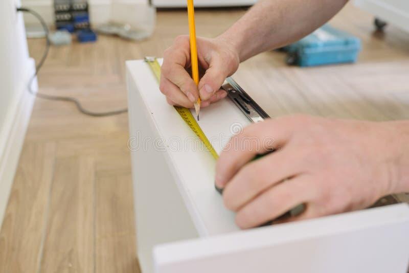 Κινηματογράφηση σε πρώτο πλάνο του εργαζομένου χεριών που κάνει τα έπιπλα, συγκεντρώνοντας την κουζίνα με τα επαγγελματικά εργαλε στοκ φωτογραφία