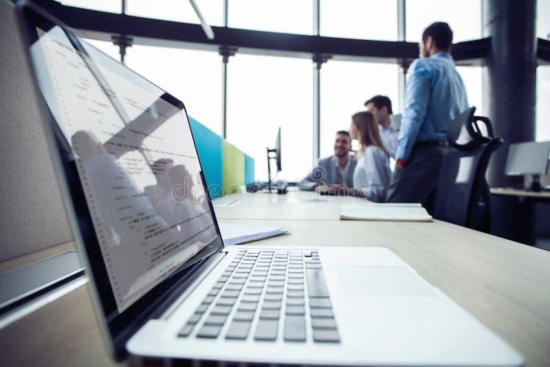 Κινηματογράφηση σε πρώτο πλάνο του εργασιακού χώρου στο σύγχρονο γραφείο με τους επιχειρηματίες πίσω Συνάδελφοι που συναντιούνται στοκ εικόνα