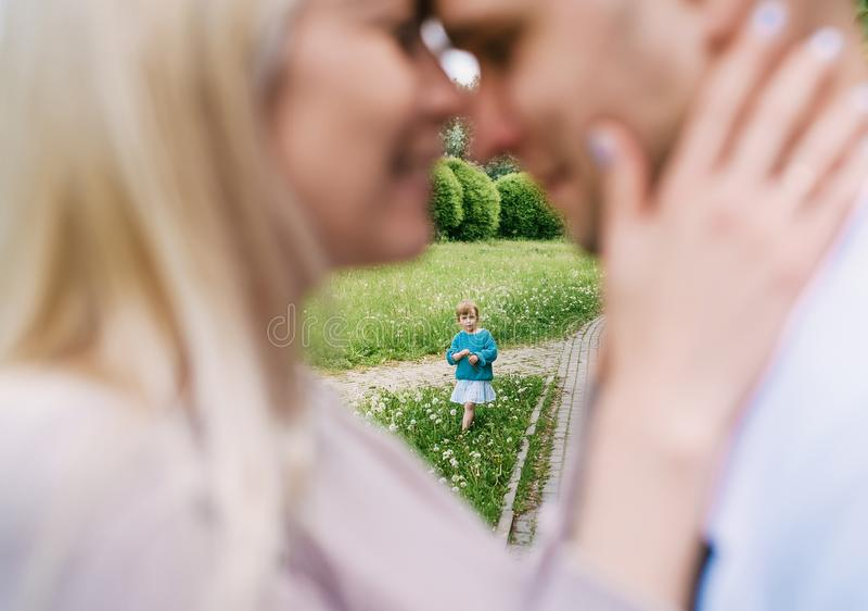 Κινηματογράφηση σε πρώτο πλάνο του ευτυχούς ζεύγους με την λίγη κόρη που φιλά πέρα από ένα υπόβαθρο πάρκων Εστίαση στα παιδιά στοκ εικόνες