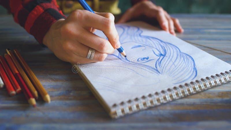 Κινηματογράφηση σε πρώτο πλάνο του θηλυκού σκίτσου ζωγραφικής χεριών στο σημειωματάριο εγγράφου με τα μολύβια Καλλιτέχνης γυναικώ στοκ εικόνα