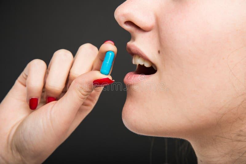 Κινηματογράφηση σε πρώτο πλάνο του θηλυκού στόματος γιατρών που παίρνει ένα χάπι στοκ φωτογραφία με δικαίωμα ελεύθερης χρήσης