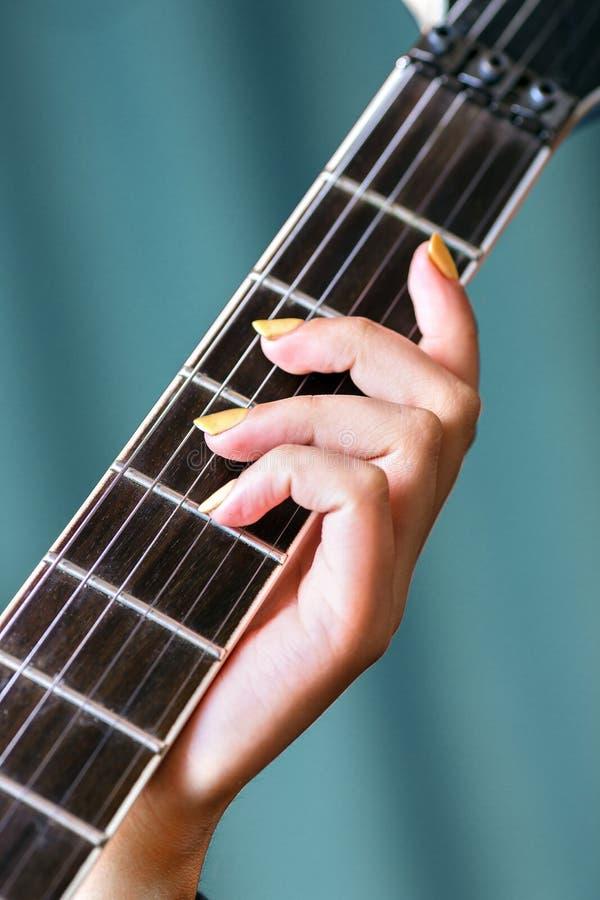 Κινηματογράφηση σε πρώτο πλάνο του θηλυκού χεριού που κρατά την ηλεκτρική κιθάρα στοκ εικόνες