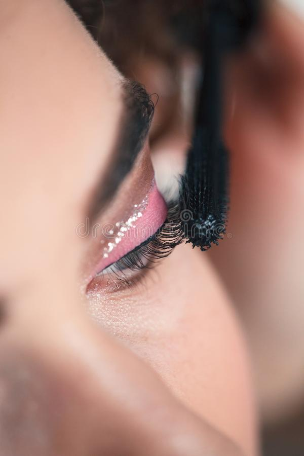 Κινηματογράφηση σε πρώτο πλάνο του καλλιτέχνη makeup που εφαρμόζει τα μάτια smokey makeup Διαδικασία επέκτασης Eyelash στοκ εικόνα με δικαίωμα ελεύθερης χρήσης