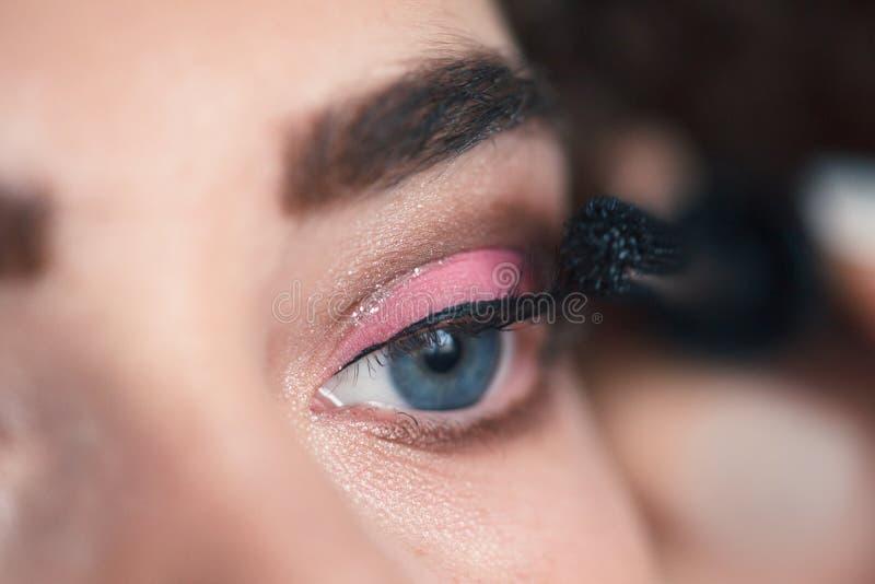 Κινηματογράφηση σε πρώτο πλάνο του καλλιτέχνη makeup που εφαρμόζει τα μάτια smokey makeup Διαδικασία επέκτασης Eyelash στοκ εικόνες