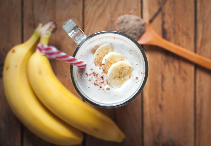 Κινηματογράφηση σε πρώτο πλάνο του καταφερτζή σπόρων μπανανών και λιναριού σε ένα γυαλί στο ξύλινο υπόβαθρο, τοπ άποψη στοκ φωτογραφία