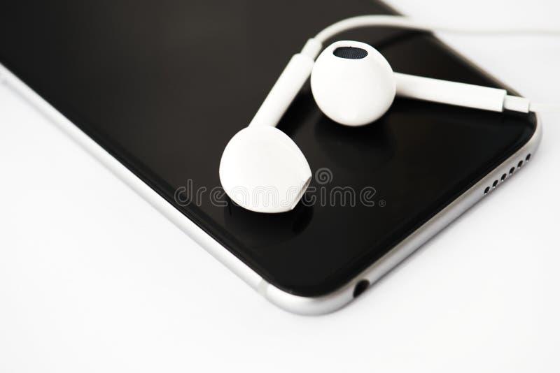 Κινηματογράφηση σε πρώτο πλάνο του κινητού τηλεφώνου με τα ακουστικά στοκ φωτογραφία