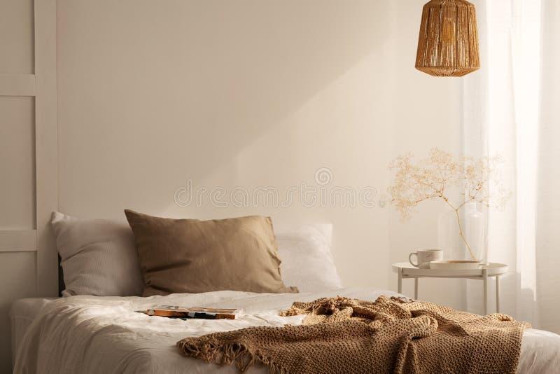 Κινηματογράφηση σε πρώτο πλάνο του κρεβατιού με το μπεζ μαξιλάρι καλυμμάτων και λινού στην ελάχιστη εσωτερική, πραγματική φωτογρα στοκ εικόνες
