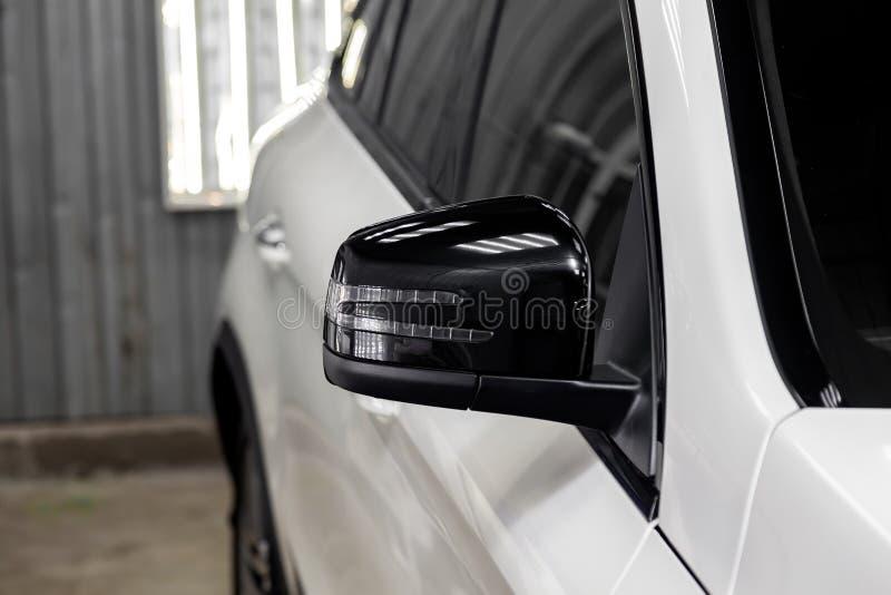 Κινηματογράφηση σε πρώτο πλάνο του μαύρου δευτερεύοντος καθρέφτη του σώματος αυτοκινήτων στο σχέδιο ενός άσπρου suv στοκ εικόνες
