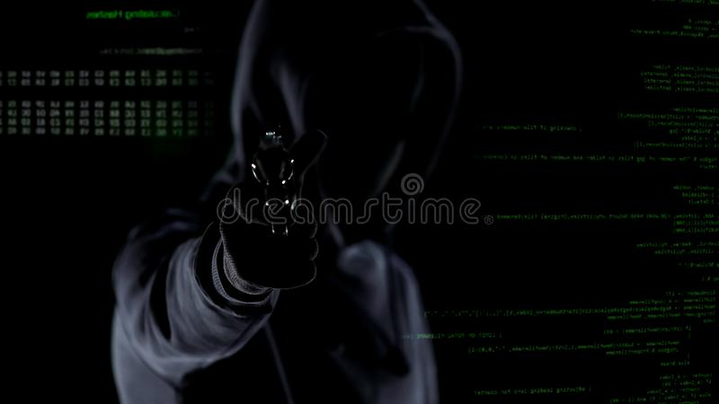 Κινηματογράφηση σε πρώτο πλάνο του με κουκούλα αρσενικού με το πυροβόλο όπλο μπροστά από το ζωντανεψοντα κώδικα PC, πυροβολισμός  στοκ φωτογραφία με δικαίωμα ελεύθερης χρήσης