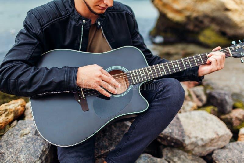 Κινηματογράφηση σε πρώτο πλάνο του νεαρού άνδρα που παίζει την ακουστική κιθάρα στην παραλία που περιβάλλεται με τους βράχους τη  στοκ φωτογραφία