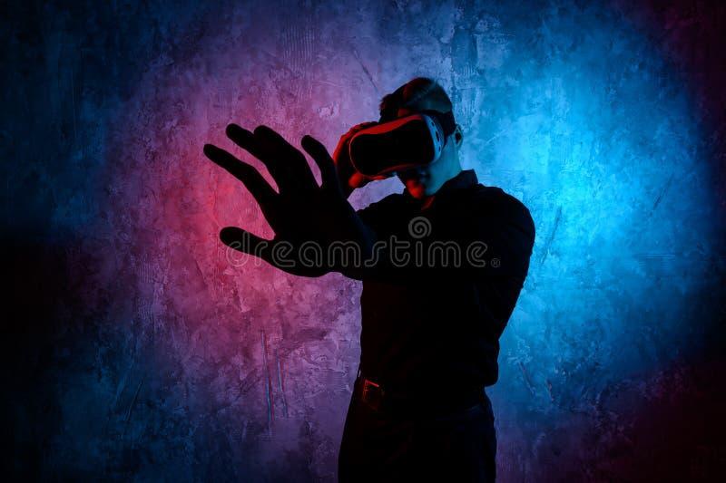 Κινηματογράφηση σε πρώτο πλάνο του νεαρού άνδρα που φορά τα προστατευτικά δίοπτρα εικονικής πραγματικότητας στο σύγχρονο στούντιο στοκ φωτογραφίες