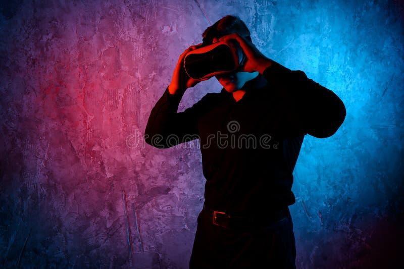 Κινηματογράφηση σε πρώτο πλάνο του νεαρού άνδρα που φορά τα προστατευτικά δίοπτρα εικονικής πραγματικότητας στο σύγχρονο στούντιο στοκ εικόνες