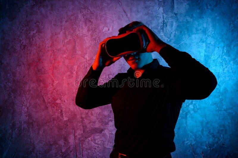Κινηματογράφηση σε πρώτο πλάνο του νεαρού άνδρα που φορά τα προστατευτικά δίοπτρα εικονικής πραγματικότητας στο σύγχρονο στούντιο στοκ φωτογραφία