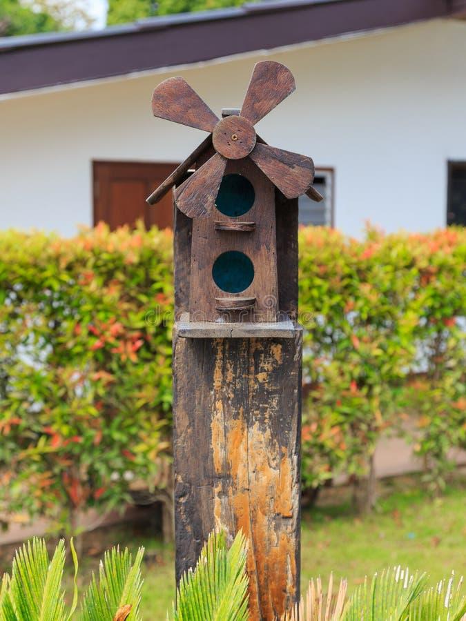 Κινηματογράφηση σε πρώτο πλάνο του ξύλινου σπιτιού πουλιών με τη στέγη αετωμάτων και του ανεμόμυλου στο γ στοκ φωτογραφία με δικαίωμα ελεύθερης χρήσης