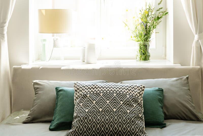 Κινηματογράφηση σε πρώτο πλάνο του πίσω μέρους του κρεβατιού με τα γκρίζα και πράσινα μαξιλάρια ενάντια σε ένα ηλιόλουστο παράθυρ στοκ φωτογραφία με δικαίωμα ελεύθερης χρήσης