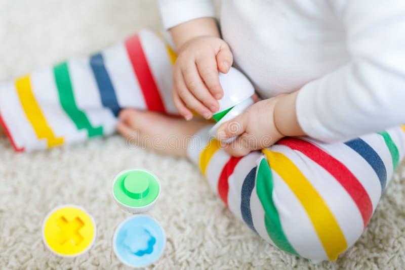 Κινηματογράφηση σε πρώτο πλάνο του παίζοντας παιχνιδιού μωρών με το εκπαιδευτικό ζωηρόχρωμο παιχνίδι διαλογέων μορφής στοκ φωτογραφία με δικαίωμα ελεύθερης χρήσης