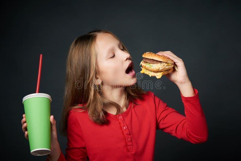 Κινηματογράφηση σε πρώτο πλάνο του πεινασμένου μικρού κοριτσιού που πηγαίνει να δαγκώσει ένα χάμπουργκερ στοκ εικόνα με δικαίωμα ελεύθερης χρήσης