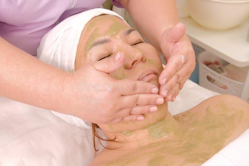 Κινηματογράφηση σε πρώτο πλάνο του προσώπου μιας γυναίκας με μια μάσκα του ακτινίδιου σε ένα σαλόνι ομορφιάς Το Beautician καθαρί στοκ εικόνες