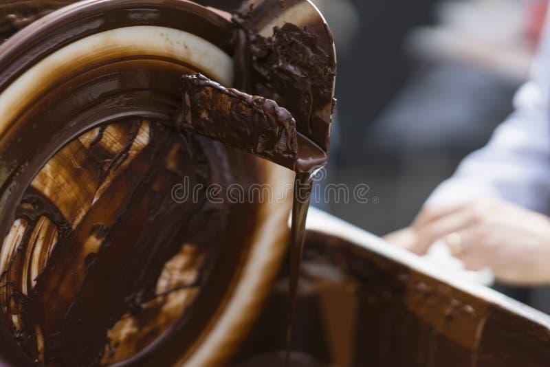 Κινηματογράφηση σε πρώτο πλάνο του ρεύματος της έκχυσης της καυτής σοκολάτας Η έννοια του νόστιμου γλυκού μεταχειρίζεται στοκ φωτογραφία με δικαίωμα ελεύθερης χρήσης