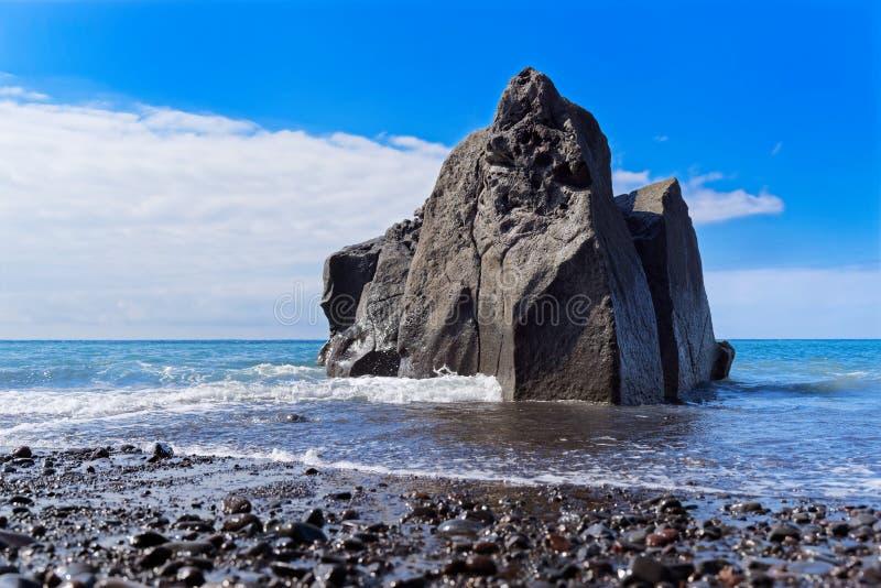 Κινηματογράφηση σε πρώτο πλάνο του σχηματισμού βράχου στην ακτή ενάντια στο μπλε ουρανό στοκ εικόνες