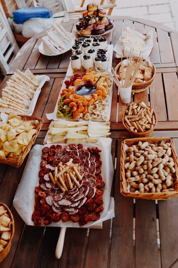 Κινηματογράφηση σε πρώτο πλάνο του τέμνοντος πίνακα με chorizo, σαλάμι, τυρί, τσιπ, ψωμί, σάντουιτς, donuts, γιαούρτι, fondue φρο στοκ φωτογραφίες