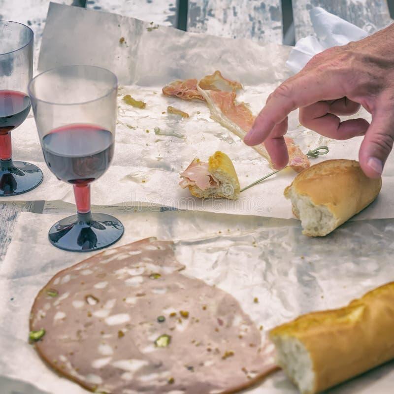 Κινηματογράφηση σε πρώτο πλάνο του χεριού ενός ατόμου, ενός κόκκινου κρασιού, ενός άσπρου ψωμιού και διαφορετικών τύπων φρέσκων λ στοκ φωτογραφία με δικαίωμα ελεύθερης χρήσης