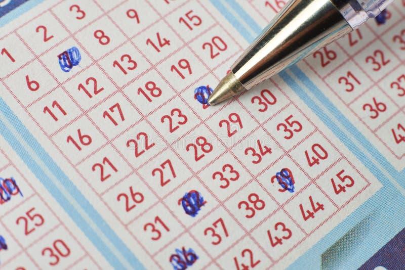 Κινηματογράφηση σε πρώτο πλάνο του χεριού που χαρακτηρίζει τον αριθμό στο εισιτήριο λαχειοφόρων αγορών με τη μάνδρα στοκ εικόνα με δικαίωμα ελεύθερης χρήσης