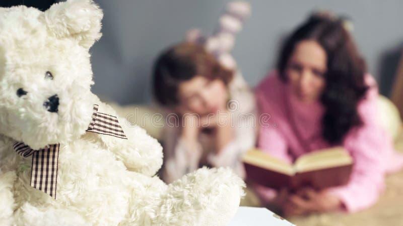 Κινηματογράφηση σε πρώτο πλάνο του χνουδωτού παιχνιδιού, mom και των παραμυθιών ανάγνωσης κορών στο υπόβαθρο στοκ εικόνες