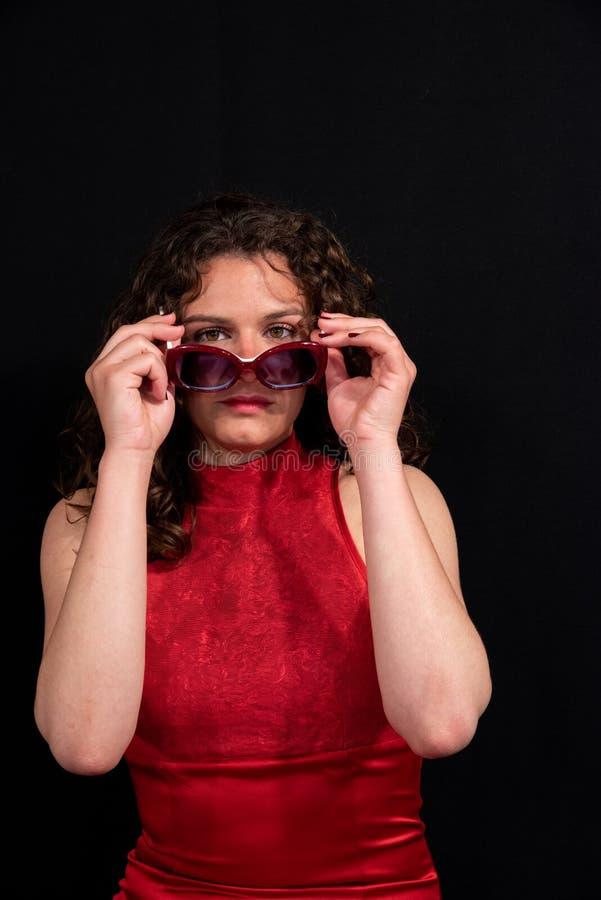 Κινηματογράφηση σε πρώτο πλάνο του όμορφου κοριτσιού με την καφετιά σγουρή τρίχα φορώντας ένα μοντέρνο ζευγάρι των γυαλιών στοκ φωτογραφία με δικαίωμα ελεύθερης χρήσης
