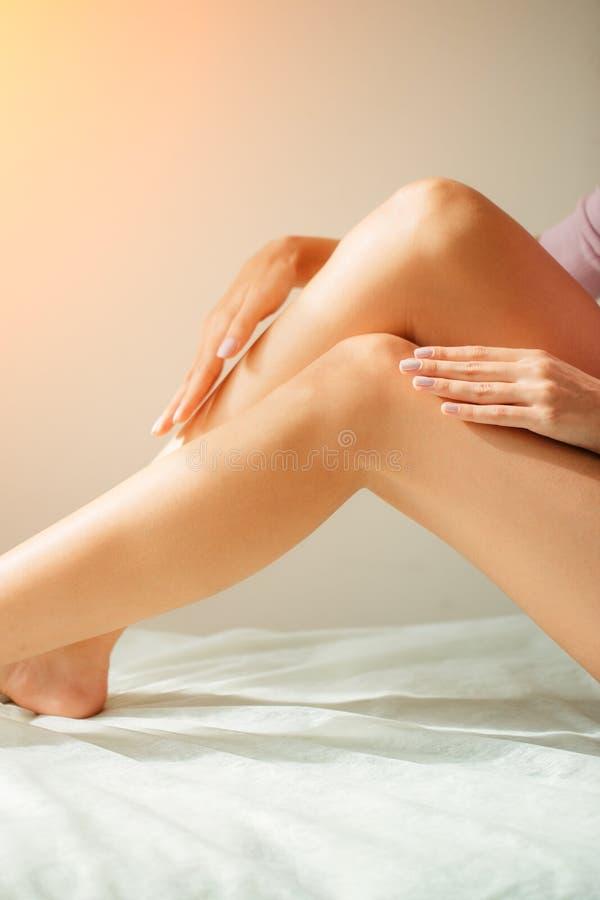 Κινηματογράφηση σε πρώτο πλάνο του όμορφου χεριού γυναικών ` s με το φυσικό μανικιούρ σχετικά με τα προκλητικά μακριά πόδια στοκ φωτογραφίες