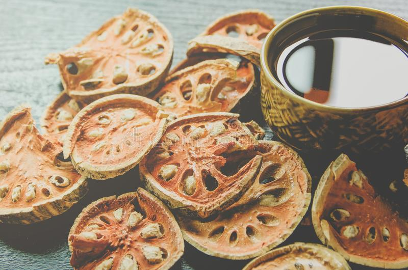 Κινηματογράφηση σε πρώτο πλάνο του bael ξηρά και τσάι και bael χυμός γυαλιού στο ξύλινο πάτωμα στοκ φωτογραφία