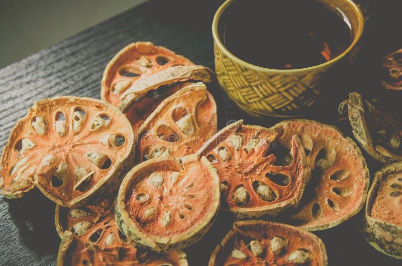 Κινηματογράφηση σε πρώτο πλάνο του bael ξηρά και τσάι και bael χυμός γυαλιού στο ξύλινο πάτωμα στοκ φωτογραφία με δικαίωμα ελεύθερης χρήσης