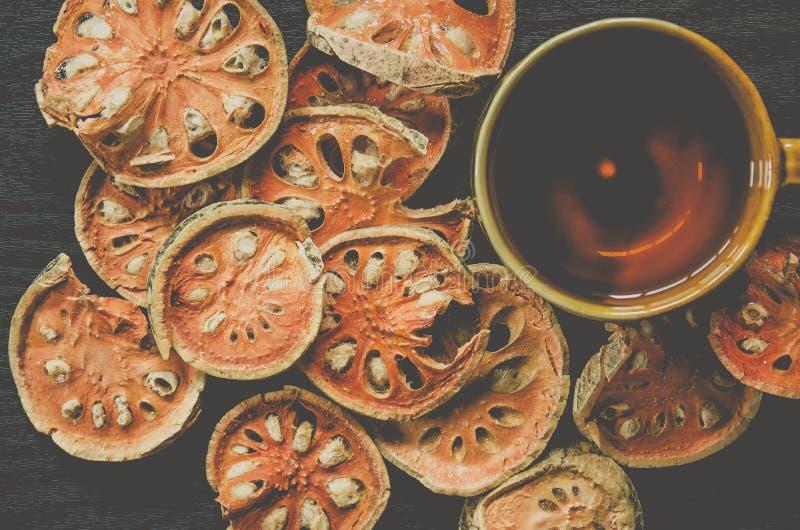 Κινηματογράφηση σε πρώτο πλάνο του bael ξηρά και τσάι και bael χυμός γυαλιού στο ξύλινο πάτωμα στοκ φωτογραφίες με δικαίωμα ελεύθερης χρήσης