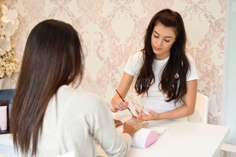 Κινηματογράφηση σε πρώτο πλάνο του beautician που εφαρμόζει την κρέμα σε ετοιμότητα γυναικών ` s που χρησιμοποιεί το brus στοκ εικόνες